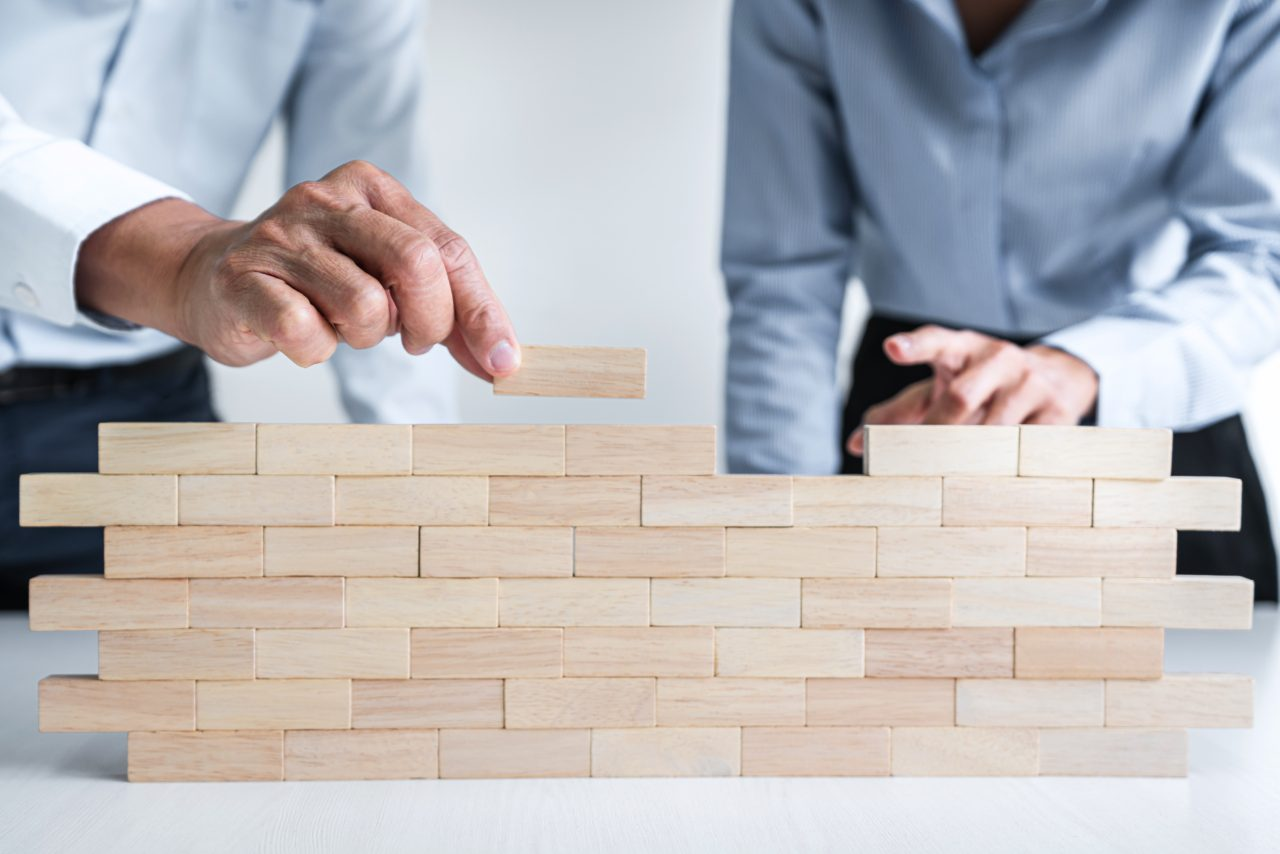 Plan and strategy in business, Risk To Make Business Growth Concept With Wooden Blocks, hand of man has piling up and stacking a wooden block.