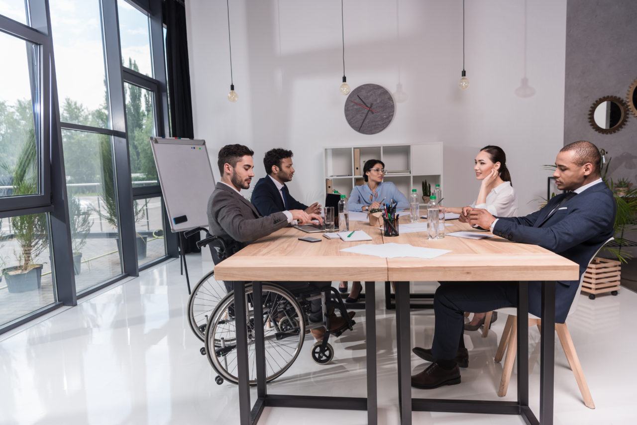 multicultural group of businesspeople discussing new idea while sitting at table in office